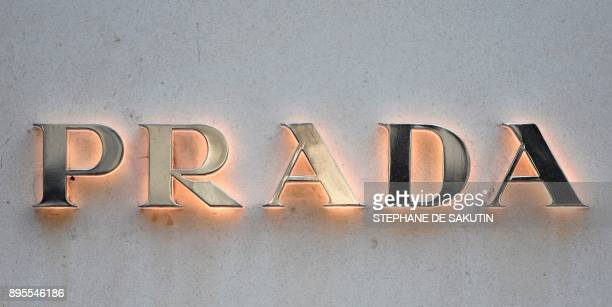 This picture taken on December 19 2017 shows a logo outside the fashion house and luxury goods Prada shop on the Avenue Montaigne in Paris ahead of...