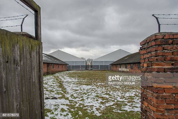 This picture taken on December 2 2016 in Oswiecim Poland shows barracks at the former German nazi camp Brick by brick plank by plank workers at the...