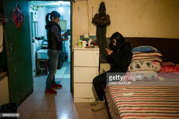 This picture taken on December 2 2016 shows a woman and her daughter in their home in a hutong in Beijing With space scarce in the city of 215...