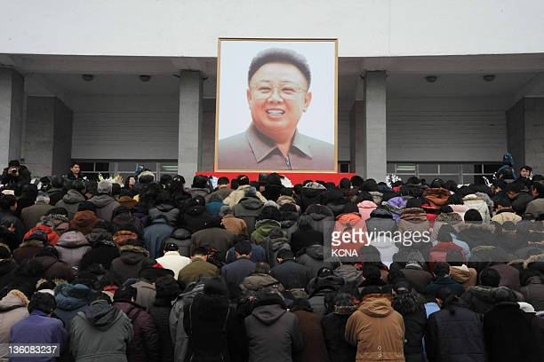 This picture taken on December 21 2011 shows Pyongyang citizens gathering to mourn in front of a portrait of late North Korean leader Kim Jongil at...