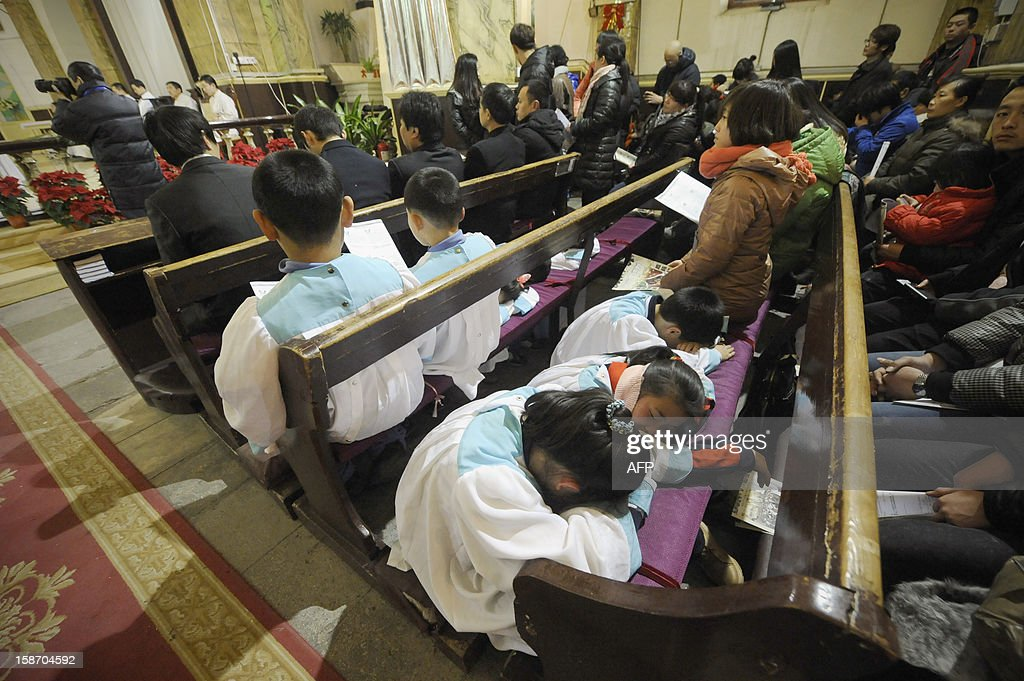 This picture taken on December 24, 2012 shows a group of young Chinese congregation members (C) resting during the Christmas Eve mass at a Catholic church in Beijing. While China does not officially celebrate Christmas, its popularity continues to grow with non-Christians keen to see and feel the experience of Christmas.