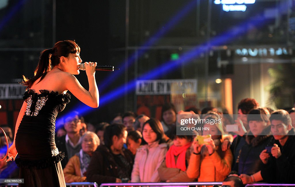 This picture taken on December 24, 2013 shows shoppers watching a singer perform at a Christmas gala at a shopping mall in Beijing, as Chinese businesses cash in on the commercial value of the Christian festival. Annual growth rates above 10 percent were once common during China's metamorphosis from a classic communist-style command economy to the state-private hybrid unleashed by reforms introduced by Deng Xiaoping in the late 1970s, and in the process, hundreds of millions of Chinese were lifted out of poverty as the economy enjoyed a decades-long boom.