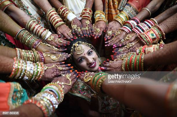 TOPSHOT This picture taken on December 24 2017 shows an Indian bride posing as others show off their decorated hands at a mass wedding in Surat some...