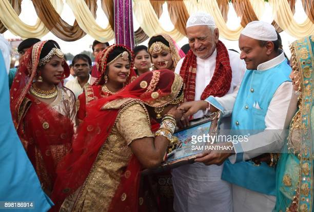 This picture taken on December 24 2017 shows an Indian Muslim bride kissing the hand of Indian businessman Maheshbhai Savani during a mass wedding in...