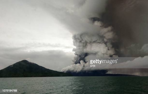 TOPSHOT This picture taken on December 26 2018 shows the Anak Krakatoa volcano erupting as seen from a ship on the Sunda Straits Indonesia on...
