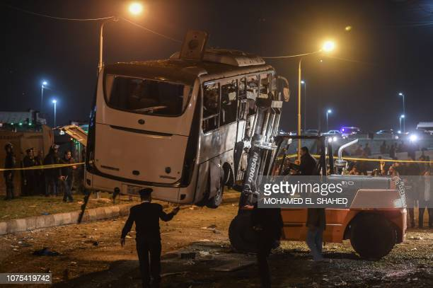 This picture taken on December 28 2018 shows a tourist bus which was attacked being towed away from the scene in Giza province south of the Egyptian...