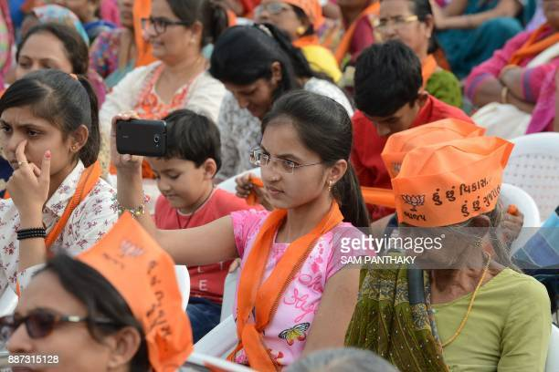 This picture taken on December 3 2017 shows a young supporter of Bharatiya Janata Party taking pictures with her mobile phone as she participates in...