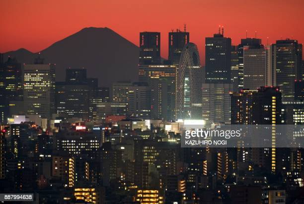 This picture taken on December 3 2017 shows Japan's highest mountain Mount Fuji at 3776 meters seen behind skyscrapers in Tokyo's Shinjuku area...