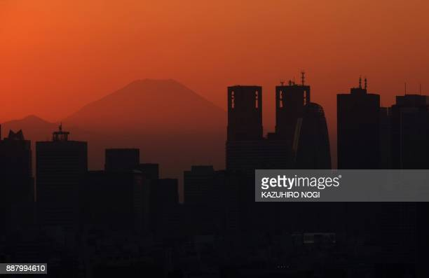 TOPSHOT This picture taken on December 3 2017 shows skyscrapers in Tokyo's Shinjuku area silhouetted at sunset in front of Mount Fuji Japan is...
