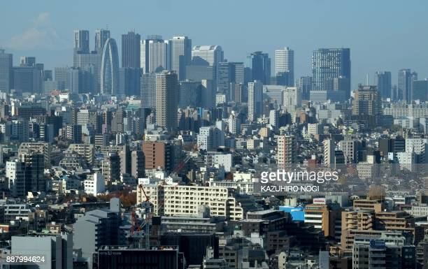 This picture taken on December 3 2017 shows skyscrapers in Tokyo's Shinjuku area and downtown streets Japan is growing twice as fast as previously...