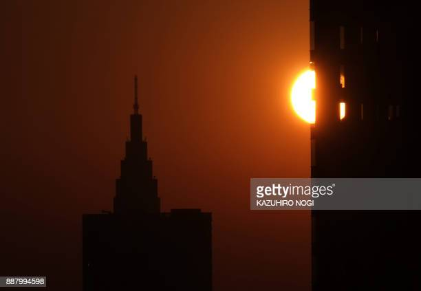 This picture taken on December 3 2017 shows the sun sinking behind a building at the sunset in Tokyo Japan is growing twice as fast as previously...
