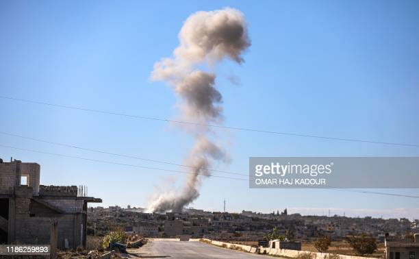 This picture taken on December 3, 2019 shows a plume of smoke rising from the town of Kafr Ruma in the south of Syria's northwestern Idlib province...