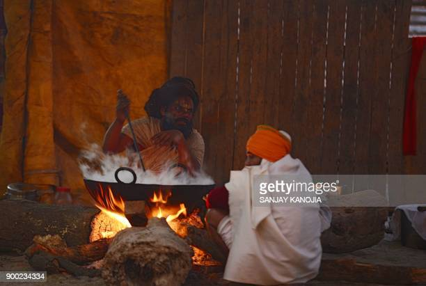 TOPSHOT This picture taken on December 31 2017 shows an Indian sadhu preparing food at a camp at Sangam ahead of the Magh Mela festival in Allahabad...