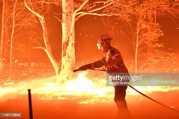 This picture taken on December 31 2019 shows a firefighter hosing down trees and flying embers in an effort to secure nearby houses from bushfires...