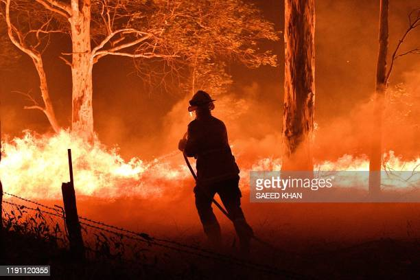 This picture taken on December 31, 2019 shows a firefighter hosing down trees and flying embers in an effort to secure nearby houses from bushfires...