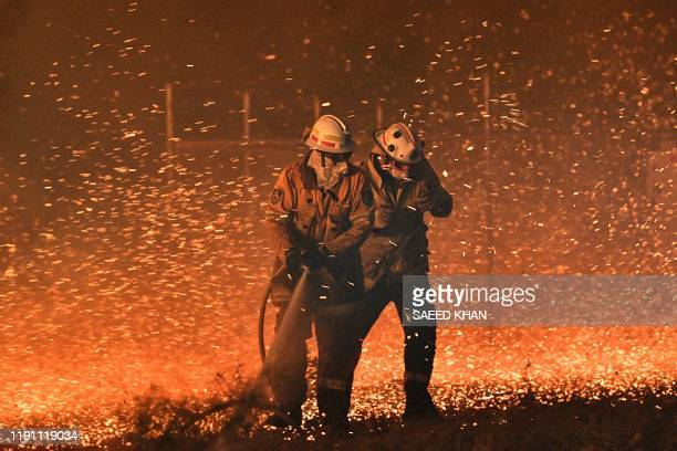 This picture taken on December 31 2019 shows firefighters struggling against the strong wind in an effort to secure nearby houses from bushfires near...