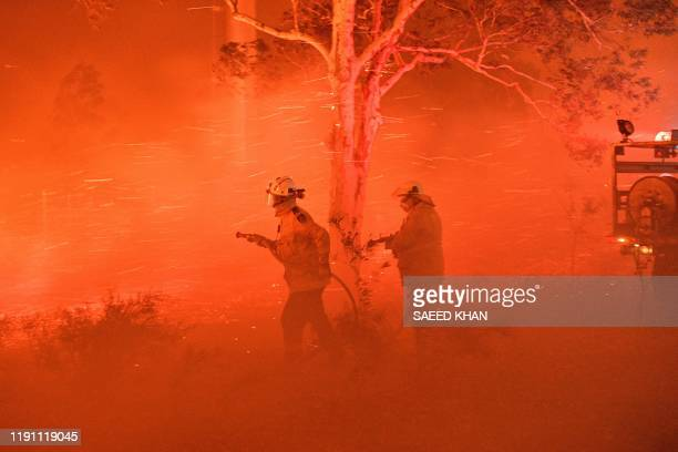 This picture taken on December 31 2019 shows firefighters struggling against strong winds and flying embers in an effort to secure nearby houses from...
