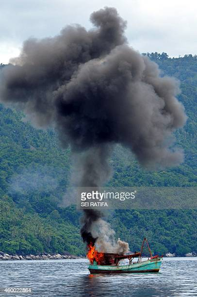 This picture taken on December 5 2014 shows a Vietnamese fishing boat in flames after Indonesian Navy officers blew up the vessel due to illegal...