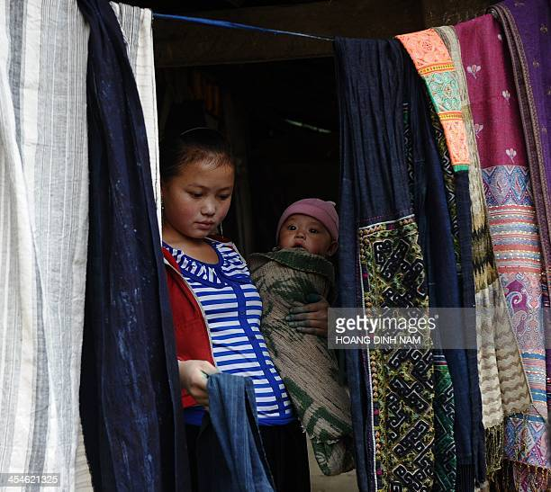 This picture taken on December 6 2013 shows a 16yearold Hmong ethnic mother with her 6month son selling Hmong ethnic traditional materials as...