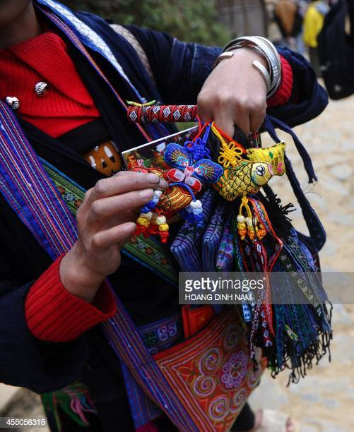 This picture taken on December 6 2013 shows a Hmong ethnic woman selling souvenir items at a village in the popular tourist district of Sapa northern...