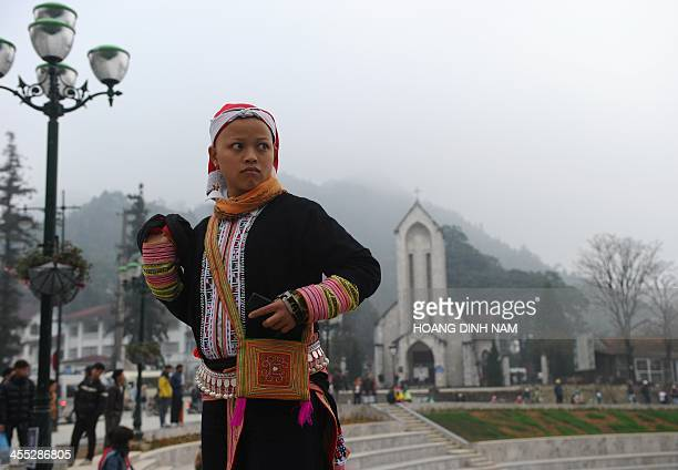 This picture taken on December 7 2013 shows a Dao ethnic woman on her Sunday best waiting for friends on the church square in downtown of the popular...