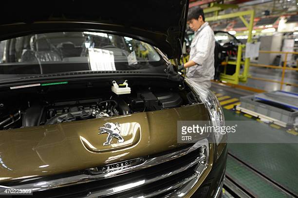 This picture taken on December 7 2013 shows a laborer working in the factory of Dongfeng PeugeotCitroën Automobile Limited in Wuhan central China's...