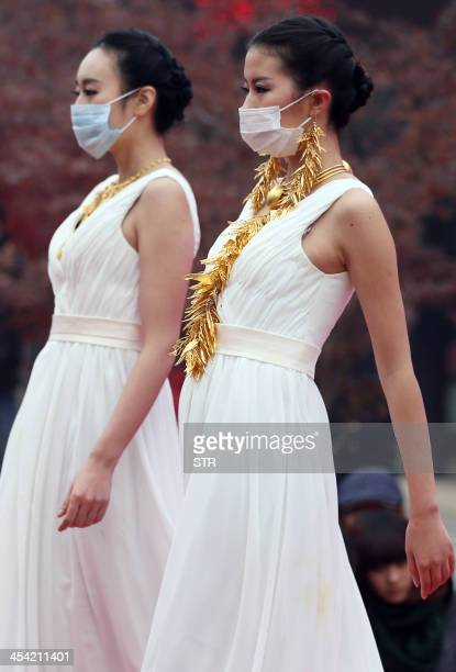 This picture taken on December 7 2013 shows models wear surgical masks as they parade a collection of gold jewelleries at a park in Nanjing east...