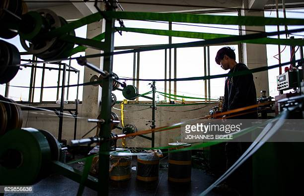 This picture taken on December 7 2016 shows a worker operating a machine producing fake 'branches' in Sun Xudan's artificial Christmas tree factory...