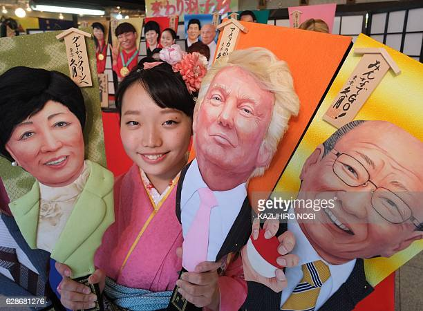 This picture taken on December 7 2016 shows Japanese traditional doll maker Kyugetsu employee Megumi Kondo in a kimono dress displaying wooden...