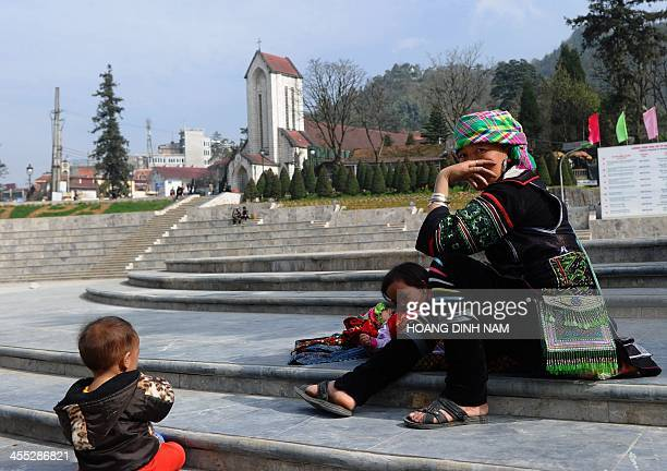 This picture taken on December 8 2013 shows a Hmong ethnic mother and her kids resting on the church square in downtown of the popular tourist...