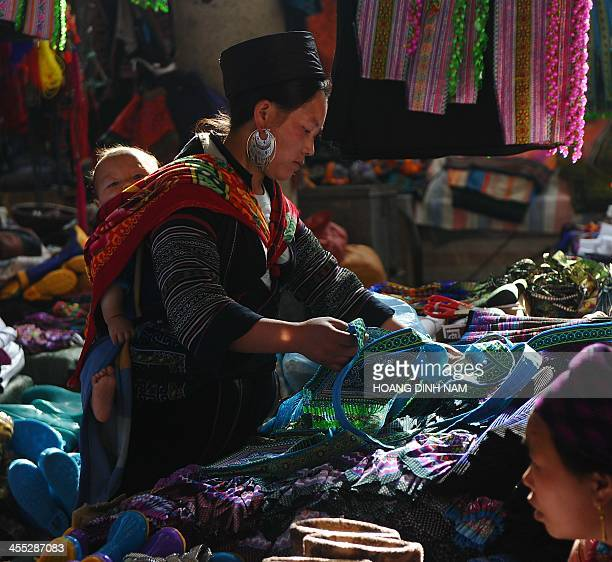This picture taken on December 8 2013 shows a Hmong ethnic woman shopping at a local market in downtown of the popular tourist district of Sapa...