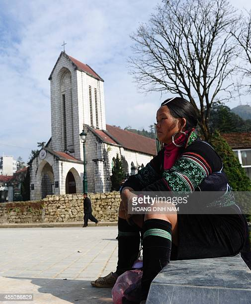 This picture taken on December 8 2013 shows a Hmong ethnic woman resting on the church square in downtown of the popular tourist district of Sapa...
