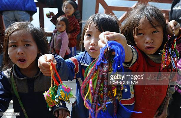 This picture taken on December 8 2013 shows Hmong ethnic children trying to sell souvenir items to tourists at a village in the popular tourist...