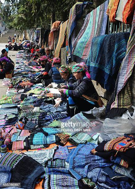 This picture taken on December 8 2013 shows Hmong ethnic women selling souvenir items made of traditional materials on a street in downtown of the...