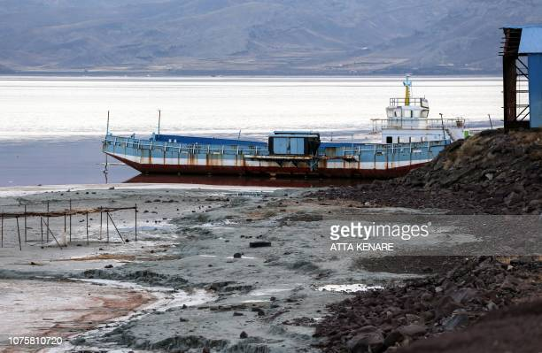 This picture taken on December 8 2018 shows a view of a ship moored by the shore of Iran's salt lake of Urmia in the country's northwest which had...