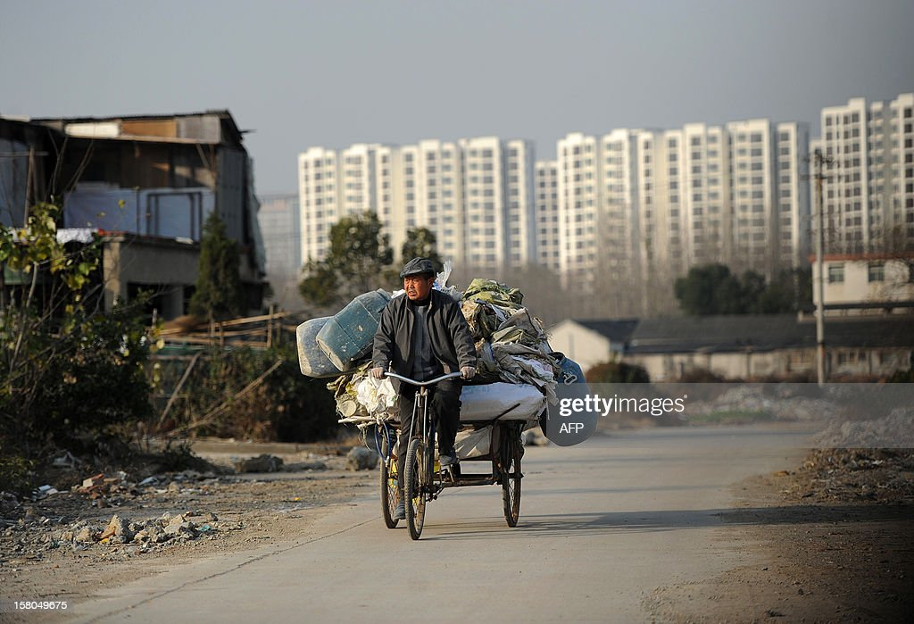 This picture taken on December 9, 2012 shows a scavenger cycling in a construction waste garbage dump in Hefei, central China's Anhui province. China's wealth gap has widened to a level where it is among the world's most unequal nations, a Chinese academic institute said in a survey, as huge numbers of poor are left behind by the economic boom. CHINA