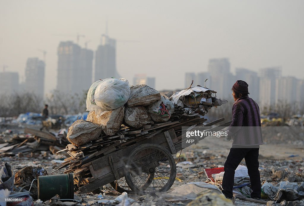 This picture taken on December 9, 2012 shows scavengers picking up useful construction waste from a garbage dump in Hefei, central China's Anhui province. China's wealth gap has widened to a level where it is among the world's most unequal nations, a Chinese academic institute said in a survey, as huge numbers of poor are left behind by the economic boom. CHINA