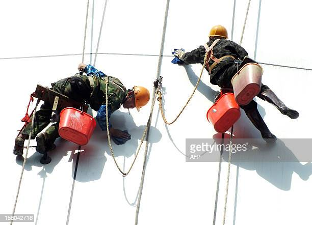 This picture taken on December 9 2012 shows two workers cleaning the facade of a building in Guangzhou south China's Guangdong province China's...