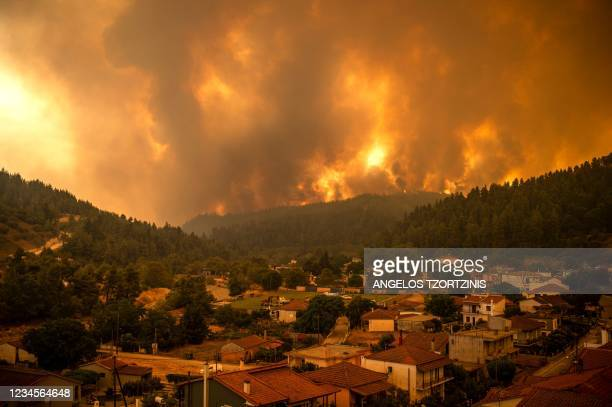 This picture taken on Evia island, second largest Greek island, on August 8, 2021 shows a wildfire moving towards the village of Gouves. - Hundreds...