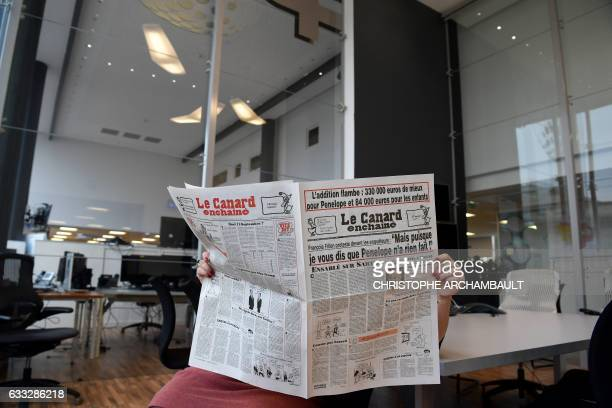 This picture taken on February 1 2017 in Paris shows a journalist reading the February 1 2017 issue of French satirical newspaper Le Canard Enchaine...