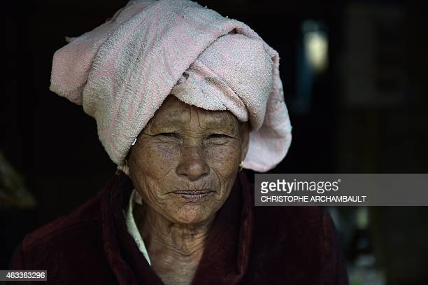 This picture taken on February 10 2015 shows a Laotian villager portrayed outside her house in Ban Napia in the northern Laotian province of...