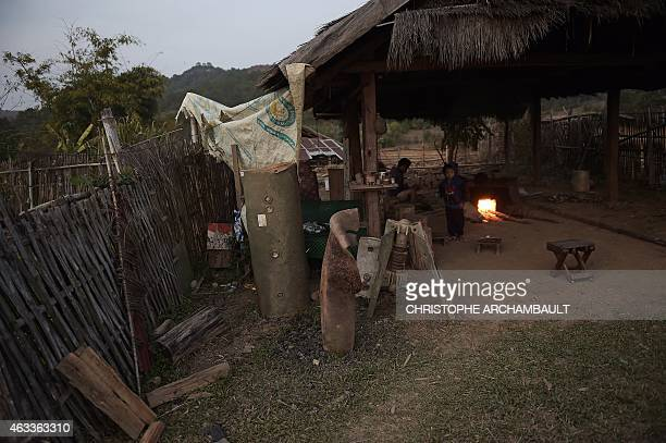 This picture taken on February 10 2015 shows Vietnam War bomb shells and parts outside the workshop of a villager and artisan in Ban Napia in the...