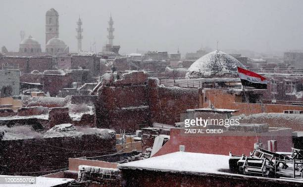 This picture taken on February 10, 2020 amidst a heavy snow storm shows a general view of the skyline of the war-ravaged old town of Iraq's northern...