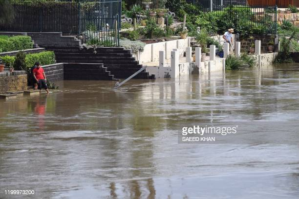 This picture taken on February 10 2020 shows residents on the banks of the swollen Georges river in Sydney waiting for water to recede Heavy rain has...