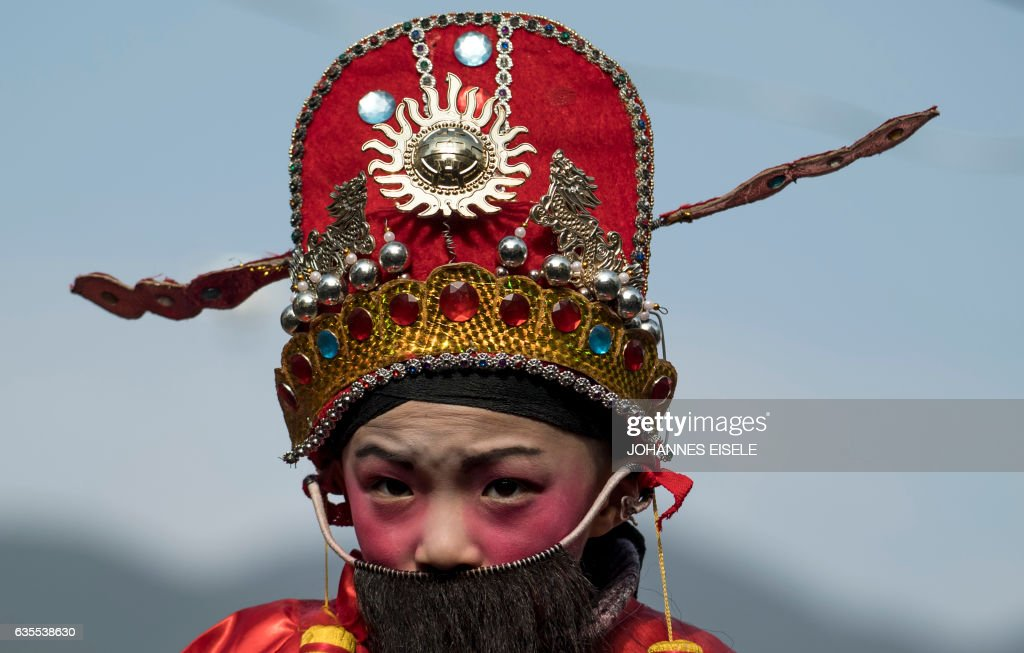 TOPSHOT - This picture taken on February 11, 2017 shows a boy in traditional clothing waiting to be paraded in a festival through the village of Luofang village in Liancheng county in China's eastern Fujian province. The ceremonies accompanied the Lantern Festival, which officially fell this year on February 11, but whose run-up and aftermath are marked by Hakka observances in Fujian. The Hakka, which means 'guest', are Chinese who speak their own eponymous dialect and have a history as wanderers that has given birth to a range of colourful cultural rituals. / AFP PHOTO / Johannes EISELE