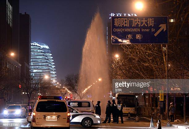 This picture taken on February 12 2014 shows a policeman watching as workers try to plug a water pipe that burst along a street in Beijing The...