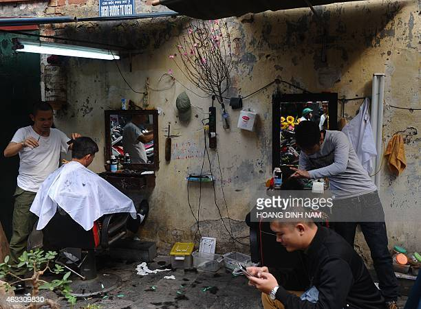 This picture taken on February 12 2015 shows men getting their hair cut ahead of 'Tet' the Lunar New Year holiday at a street barber shop in the old...
