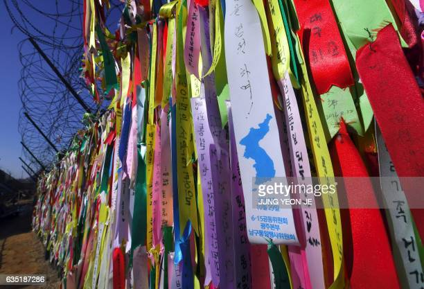 TOPSHOT This picture taken on February 12 2017 shows ribbons with inscriptions calling for peace and reunification hung from a military barbed wire...