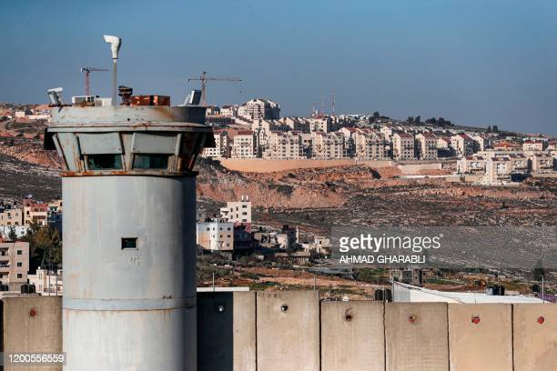 This picture taken on February 13 2020 shows a view of a watchtower and a section of Israel's controversial separation barrier on the outskirts of...