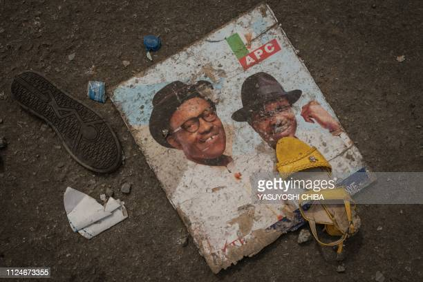 TOPSHOT This picture taken on February 13 shows shoes and a picture of Nigeria's President Muhammadu Buhari lying the ground in front of the main...